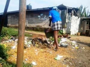 On déverse des ordures devant une maison. Le propriétaire des lieux, assis à quelques mètres, ne dit mot. On l'a compris, on vit au milieu d'ordures à Bilongué. Crédit-photo: @JosianeKouagheu